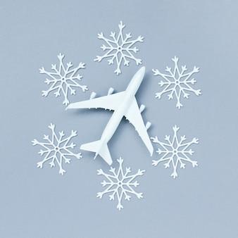 눈송이로 둘러싸인 회색 배경에 비행기. 겨울철 새해 여행 및 비행 개념