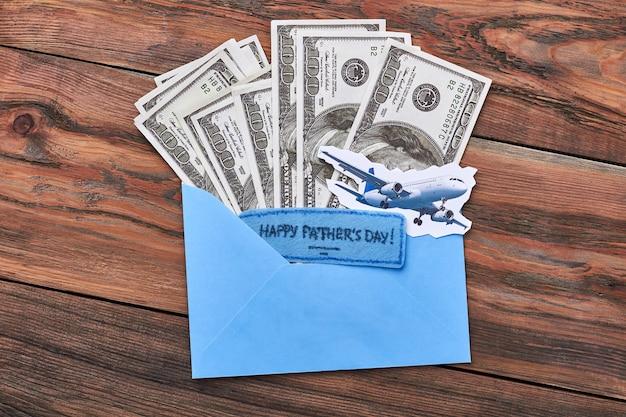 紙とお金の平面。ドル、封筒、父の日カード。贈り物としての高価な旅行。