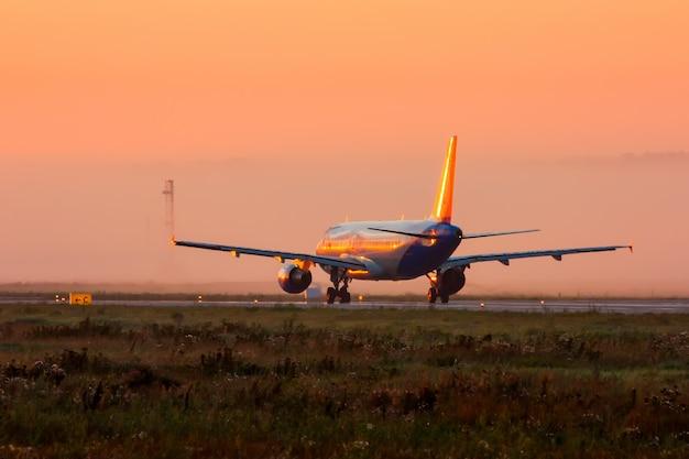 霧の早い朝の滑走路の飛行機