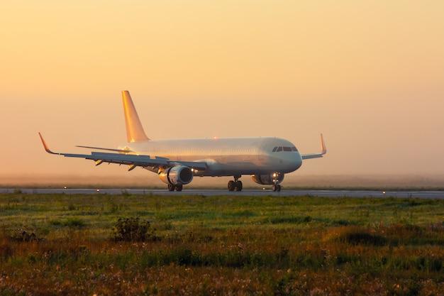 霧の早い朝の誘導路の飛行機
