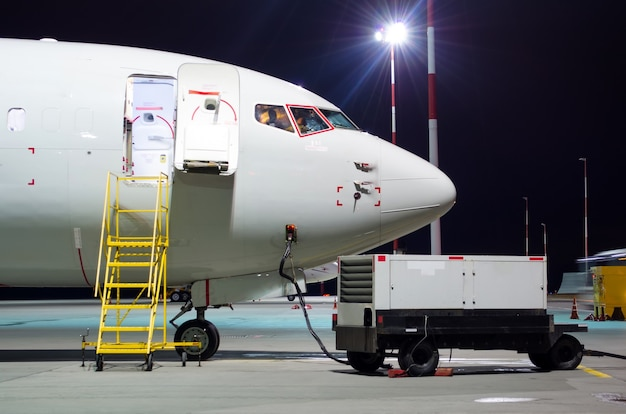Plane parked at the airport at night, view nose cockpit.
