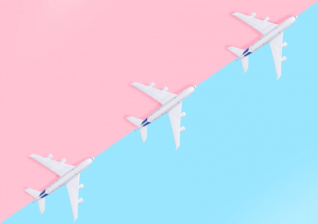Plane on a pastel pink and blue background with top view and copy space.
