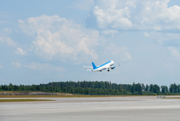 The plane takes off from the runway at the airport.