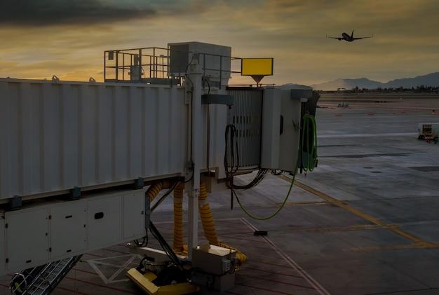 미국 애리조나 주 피닉스와 스카이 하버 공항의 공항을 연결하는 데 사용되는 탑승 교에서 붉은 석양으로 이륙하는 비행기