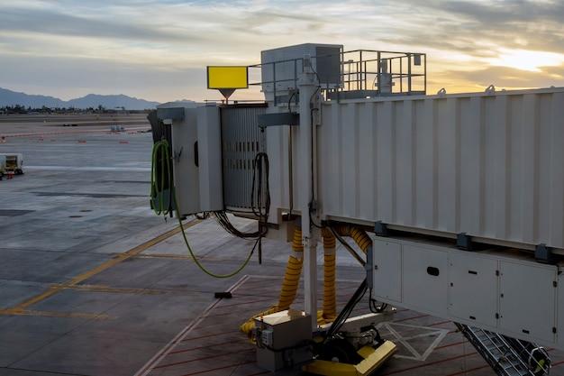 공항을 연결하는 데 사용되는 탑승 교에서 붉은 석양으로 이륙하는 비행기