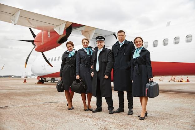 비행기 제트 근처 활주로에 서있는 비행기 팀. 현대 여객기. 웃는 여자와 남자는 제복을 입는다. 조종사, 승무원 및 스튜어디스. 팀워크. 민간 항공. 항공 여행 컨셉