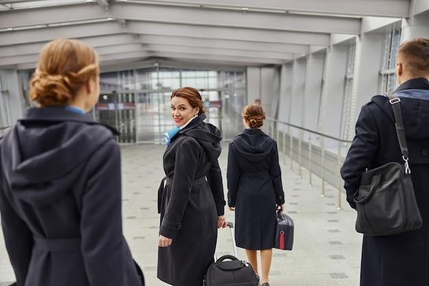 飛行機のチームは荷物を持って近代的な空港の入り口まで歩きます。女性と男性の背面図は制服を着ています。客室乗務員とスチュワーデス。チームワーク。民間商用航空。空の旅のコンセプト