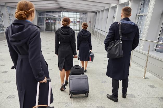 現代の空港の入り口まで荷物を持って歩く飛行機チーム。女性と男性の背面図は制服を着ています。客室乗務員とスチュワーデス。チームワーク。民間商用航空。空の旅のコンセプト