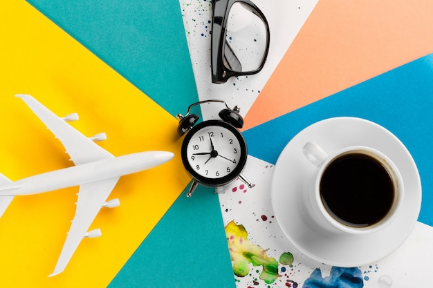 Plane toy, glasses, coffee cup and alarm clock