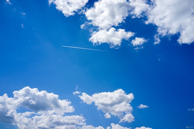 Plane trail in clear sky with clouds