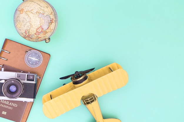 Plane travel accessories objects top view flatlay on teal pastel