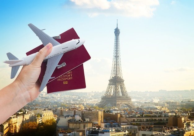 Plane travel concept, hand holding passports with plane, paris france cityscape in background
