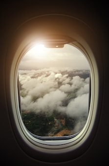 Plane window view with blue sky and clouds at sunset.