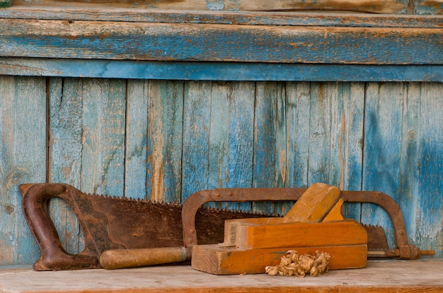 Planer, hacksaw and a saw on an old wooden table, chips