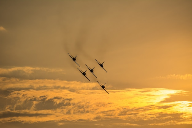 Planes in formation flying on sky at sunset time