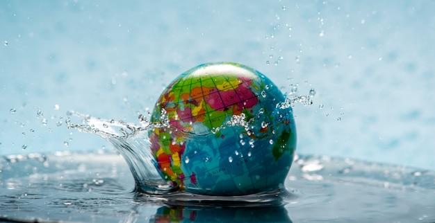 水しぶきのある透明な水の中の地球の形をした惑星地球