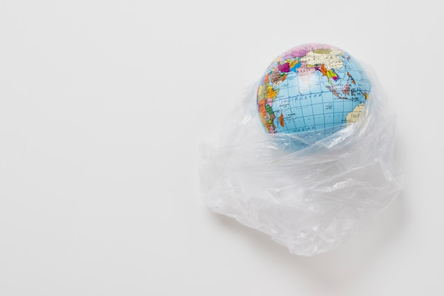 Planet in plastic bag on grey background