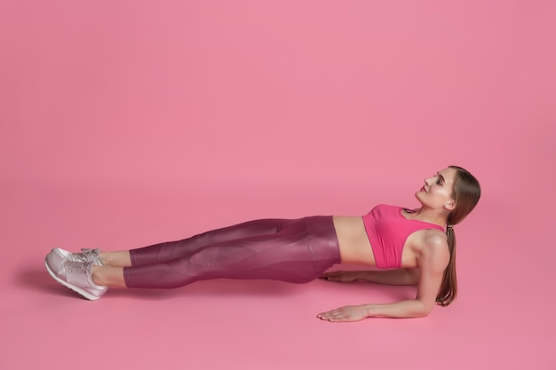Plank balanced. beautiful young female athlete practicing , monochrome pink portrait. sportive fit caucasian model training. body building, healthy lifestyle, beauty and action concept.