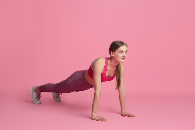 Plank balanced. beautiful young female athlete practicing in studio, monochrome pink portrait.
