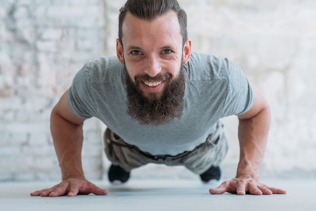 Plank hold. smiling man training. strength and power exercising. athletic lifestyle.