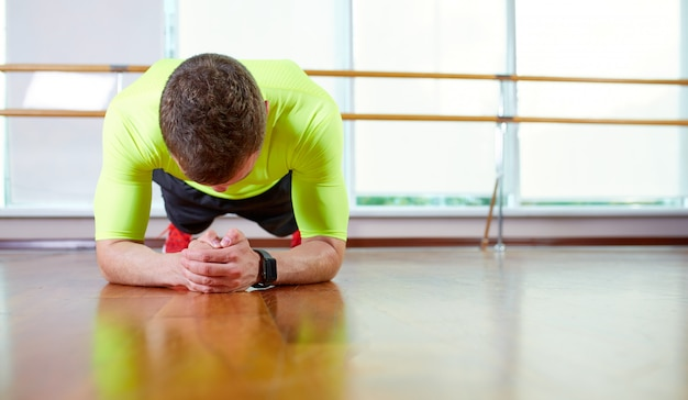 Plank it confident muscled young man wearing sport wear and doing plank position while exercising on the floor in loft interior