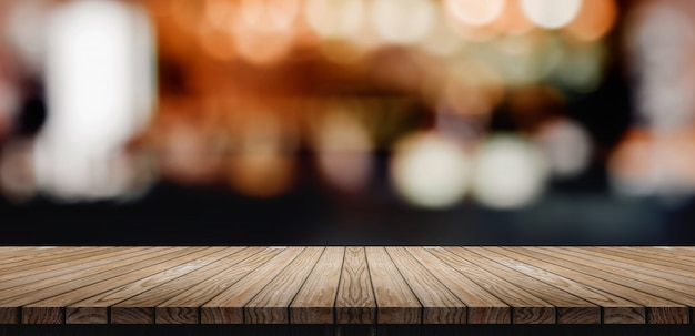 Plank wood table top with blur nightclub bar counter with bokeh light background