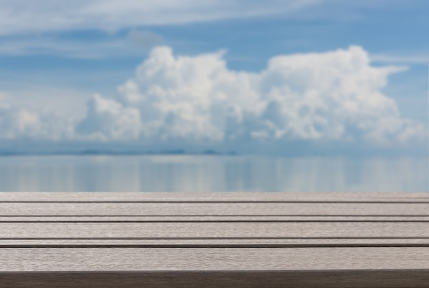 Plank wood table top  with blurred blue sea sky summer background