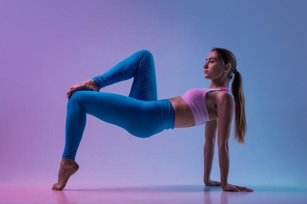 널빤지. 네온 불빛에 그라데이션 스튜디오 배경에 고립 된 낚시를 좋아하는 젊은 여성 훈련. 운동적이고 우아한. 현대 스포츠, 액션, 모션, 청소년 개념. 아름 다운 백인 여자 연습입니다.