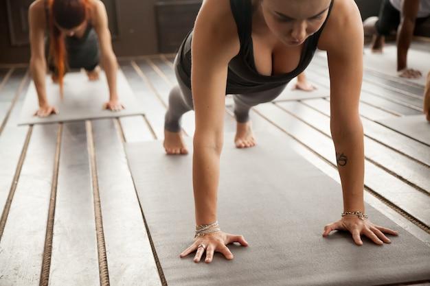 Женщина и группа спортивных людей в представлении plank