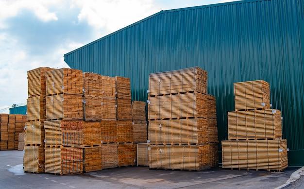 Доски в панелях на складе магазина. вид сбоку. хранение на открытом воздухе. заготовка древесины