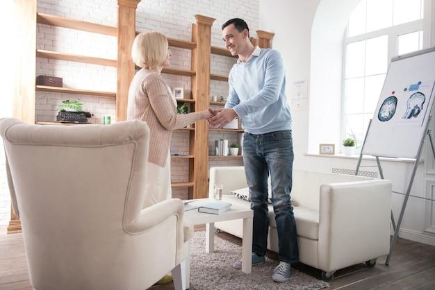 계획된 회의. 긍정적 인 고위 여자와 악수하는 동안 서있는 남자