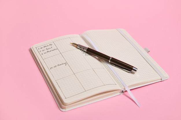 일기에 표시된 시간에 따른 플래너 템플릿 및 하루 일정과 열린 노트북에 잉크 펜이 놓여 있습니다. 비즈니스 책 일기, 사무실 주최자 계획. 분홍색 배경, 복사 공간