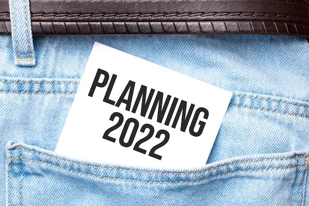 ジーンズのポケットから突き出た白い紙に2022年の言葉を計画。ビジネスコンセプト。
