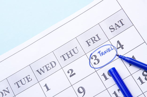 パペットカレンダーの青いフェルトペンで旅行日としてマークされた旅行コンセプトの金曜日を計画しています...