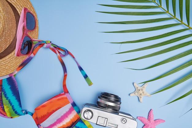 旅行旅行と旅についての計画。ビキニ、カメラ、帽子、サングラスと青い背景の上のフラットレイ旅行アクセサリー。上面図、旅行または休暇の概念。夏の背景。