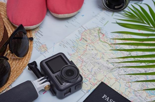 Планирование путешествия поездка и путешествие. плоские дорожные аксессуары на карте с обувью, шляпой, паспортами, деньгами, планшетом, смартфоном. вид сверху, путешествия или концепция отпуска.