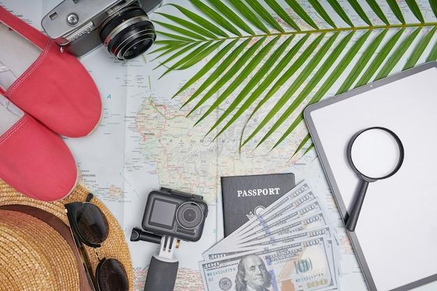 旅行旅行と旅についての計画。靴、帽子、パスポート、お金、タブレット、スマートフォンを備えた地図上のフラットレイ旅行アクセサリー。上面図、旅行または休暇の概念。