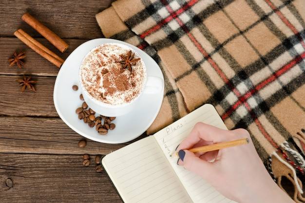 Planning in a cafe. mug latte, a female hand writing in a notebook with a pencil. top view