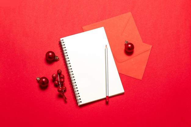 Планирование концепции. список целей вид сверху с блокнотом, ручкой, елочные шары, почтовая карточка на красном столе