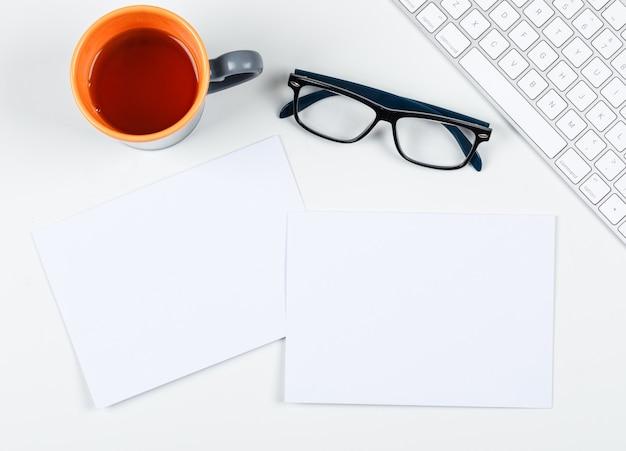 一杯のお茶、眼鏡、紙、白い背景の上のキーボード、テキスト、トップビューのためのスペースのコンセプトを計画します。横長画像