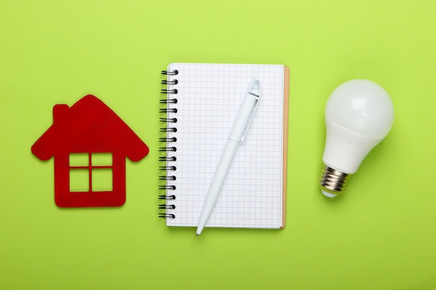 Planning energy saving. house figurine and energy-saving light bulb, notebook on green background. top view
