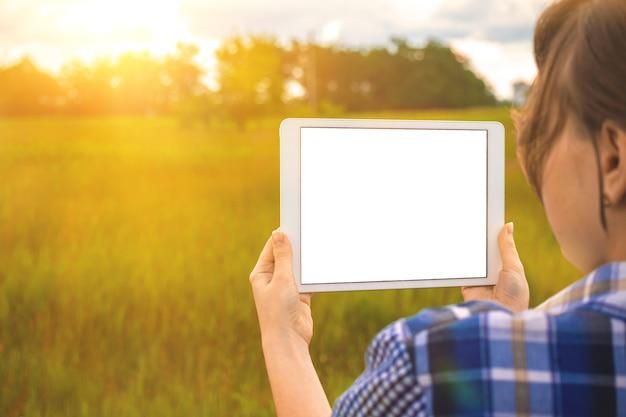建物の土地の計画、少女は日没時のフィールド、自然の背景、コピースペースの写真の横にタブレット画面のモックアップを保持します。