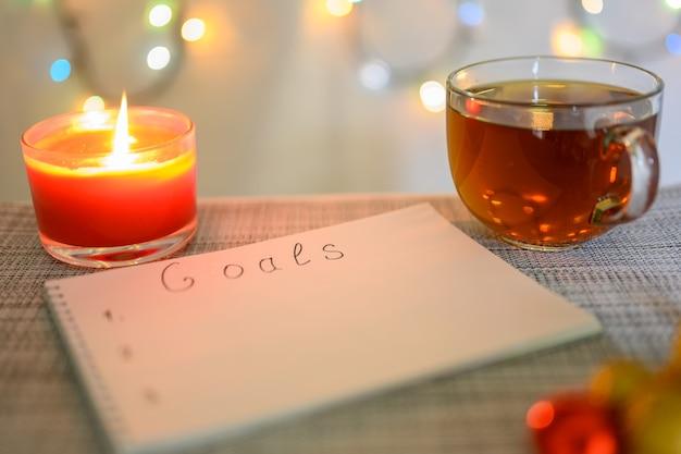 Планирование целей на следующий год с рождественским фоном, горящей свечой, чашкой чая и сверкающей гирляндой.