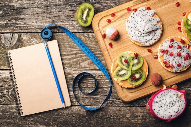 健康的な食事のコンセプトを計画します。トレーニングとフィットネスダイエット。フルーツトースト、測定テープ、木製のテーブルに空のノートブック。果物で痩身プラン。トップビュー、コピースペース
