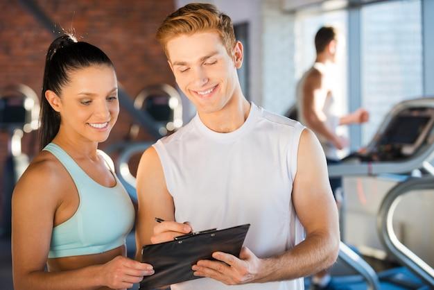 Планирует свое время в тренажерном зале. красивый молодой мужчина-инструктор стоит рядом с красивой женщиной и показывает что-то в своем буфере обмена, пока люди бегают на беговой дорожке на заднем плане
