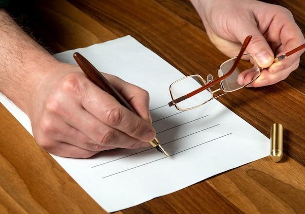 데스크탑의 작업 환경에서 계획합니다. 펜으로 빈을 채우는 인간 손의 클로즈업