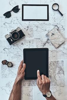 旅の計画。サングラスとデジタルタブレットを使用して男の上面図をクローズアップ
