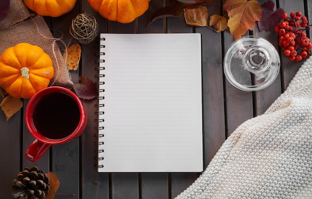 Planning to do list. autumn mood composition on a wooden table with pumpkins, rowan and leaves. open notepad and black coffee in the red cup and on grey wooden table, warming drink