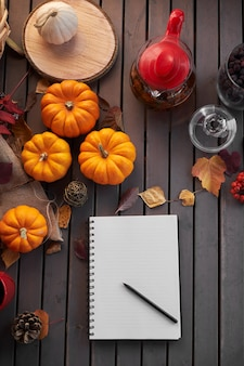 Planning to do list. autumn mood composition on a wooden table with pumpkins, rowan and leaves.