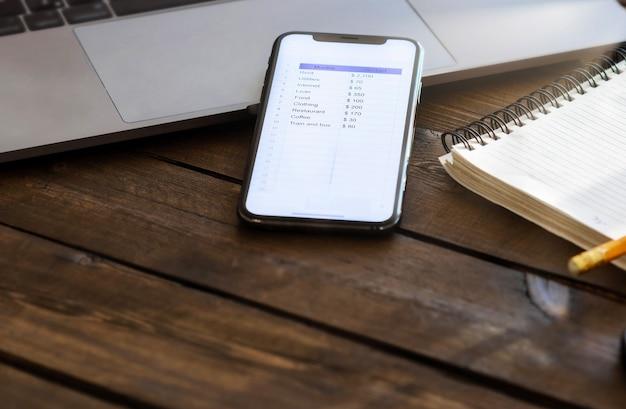 Планирование ежемесячной концепции домашнего финансирования. смартфон со списком расходов на месяц на деревянном столе